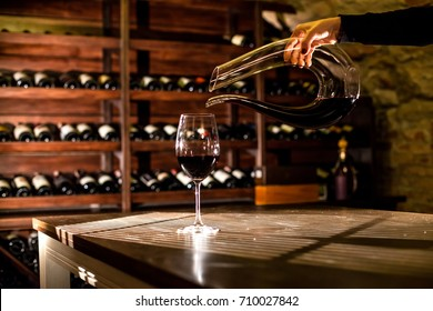 Hand holding a bottle of wine. Wine pouring into a glass. Wine vault location.