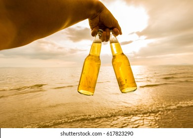 Hand holding a bottles of Beer on the beach at sunset time