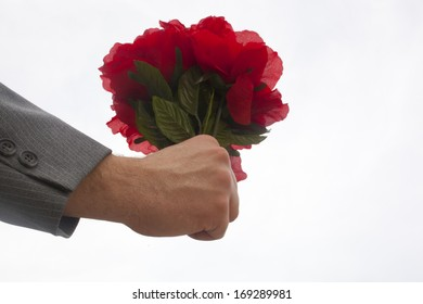A hand holding a bouquet of plastic red flowers