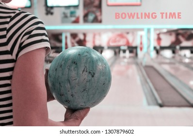Hand holding bowl and prepare for strike in blurred bowling alley background.Close up view
