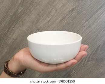 Hand holding a bowl. wooden background