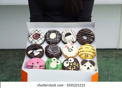 Hand holding box of various doughnuts, Different type of donuts.