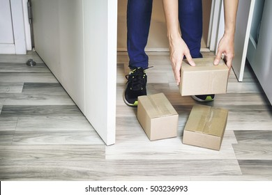Hand holding boxes at the front door, Receiving package from parcels delivery service, Online shopping. (Color Process)