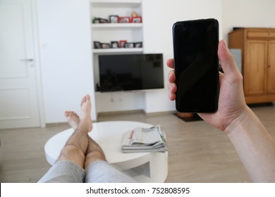 A hand holding a brand new mobile phone with an empty, black screen. The person's feet and legs are on the living room table. On the background, a television with black screen is hanging from the wall