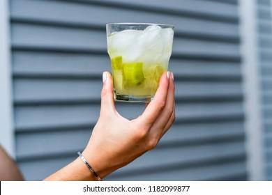 Hand holding up a Brazilian caipirinha cocktail