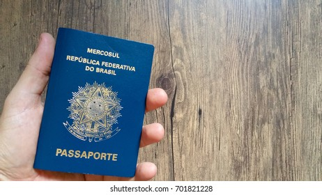 Hand holding Brazilian passport on wooden background
