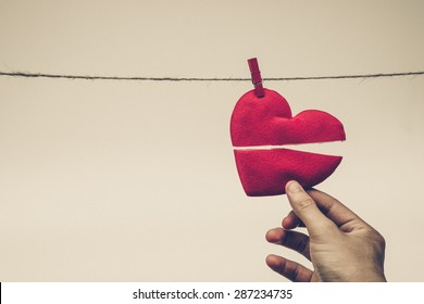hand holding broken red heart hung on rope