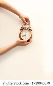 Hand holding bronze watch on white paper background. Precious time concept. RUnning out of time concept.