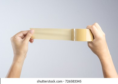 Hand holding brown packaging tape roll on white background
