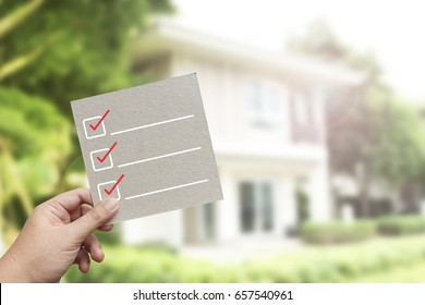 Hand holding brown paper with check mark symbol against new house background