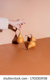 Hand holding bruised pears against brown backdrops with harsh sunlight.