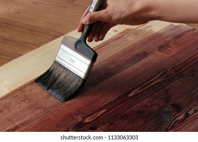 Hand holding a brush applying paint on a wooden surface.