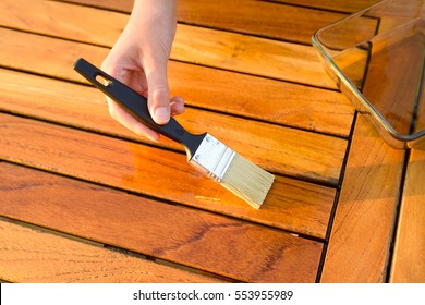 hand holding a brush applying varnish paint on a wooden garden table - painting and wood maintenance oil-wax