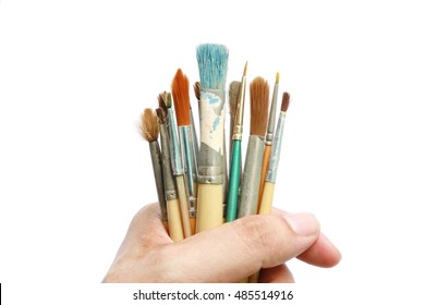 Hand holding brush isolated on white background, Hand hold  many brush for oil color paint. Artist tool and equipment.