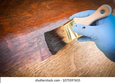 Hand holding brush shows how to apply brown mahogany stain to raw oak wood furniture or floor.