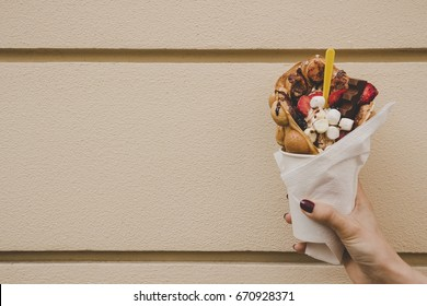 Hand holding bubble waffle with fruits, chocolate and marshmallow, with copy space.