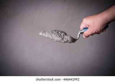 Hand holding a bucket trowel with cement mortar in construction site