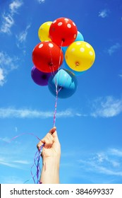 Hand holding a bunch of colorful balloons flying in the sunny blue sky, house and trees in the background.