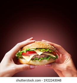 Hand holding a burger in a darkbackground. Eating and healthy concept, restaurant food concept.