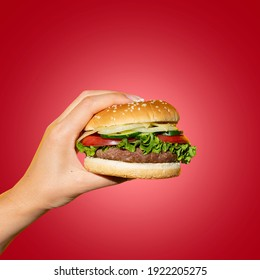 Hand holding a burger in a hot red background. Eating and healthy concept, restaurant food concept.