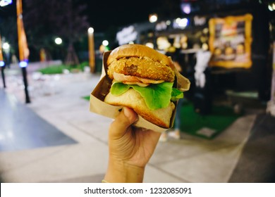 Hand Holding A Burger on Abstract Blur Foodtruck Background. Concept Eating And Healthy, Fast food
