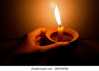 Hand holding a burning candle in pot