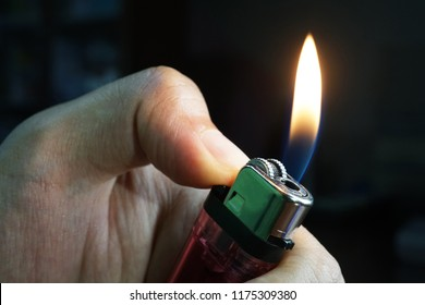 Hand holding burning gas lighters on dark background, Portable device used to create a flame, Close up