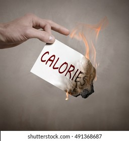 "Hand holding a burning piece of paper with the inscription "" Calories """