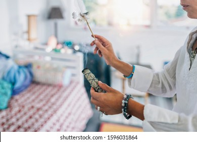 Woman's hand holding burning sage smudge stick, spreading the smoke around with white feather, blessing and cleansing home from negative energies