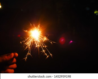Hand holding a burning sparkler firework, Happy new year and Merry christmas concept, Happy holidays, Female hand holding a burning sparkler, Abstract blurred of Sparklers for celebration.