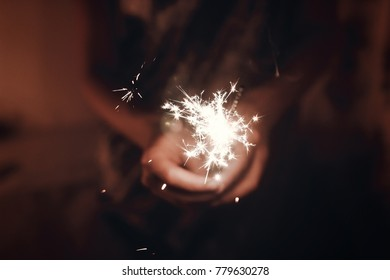 hand holding a burning sparkler firework bengal light. space for text. burning sparks closeup in female hand in dark. happy new year and merry christmas concept. happy holidays