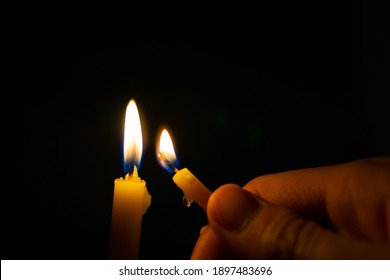 Hand holding burning yellow candle to light candle in the dark