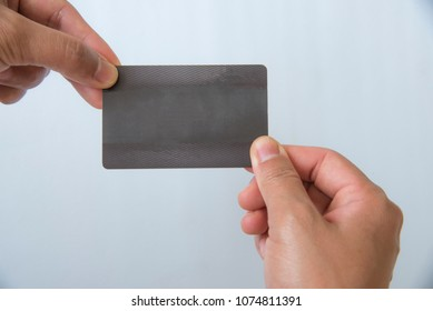 Hand holding business black card on white background.