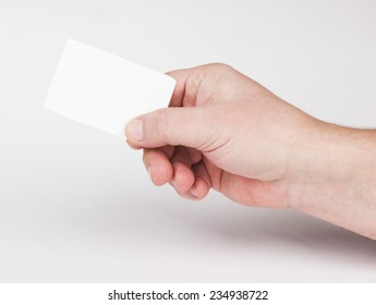 Hand holding a business card on a gray background