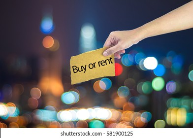 Hand holding a buy or rent sign made on sugar paper with city light bokeh as background