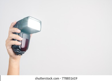 Hand holding camera  external flash speed light on white background