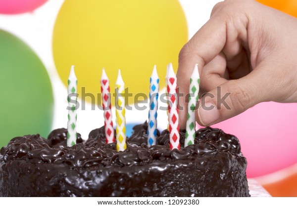 hand holding candles on top of cake