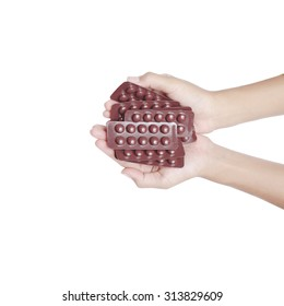 hand holding capsules and pills on white background