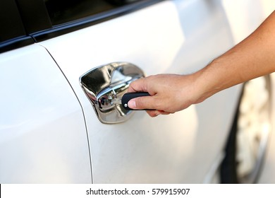 Hand holding car keys to unlock or lock the white car.Woman with car key.selective focus.
