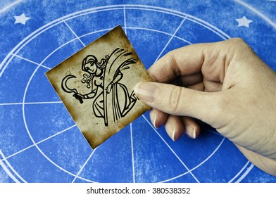 hand holding a card with sign of virgo