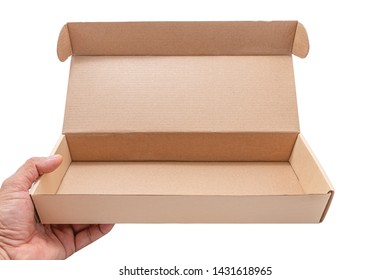 Hand holding cardboard box opened empty isolated on white background. The brown parcel cardboard box for packages delivery. Selective focus. Horizontal Image.