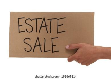 Hand holding up a cardboard estate sale sign