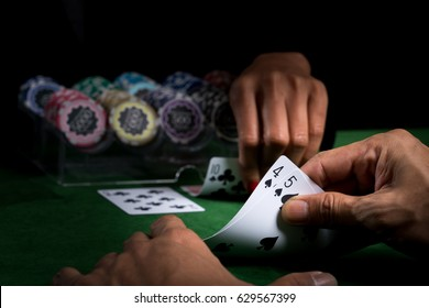 A hand holding the cards show face values over the opponent to win a blackjack game on green table and blurry stacked chips background in the casino
