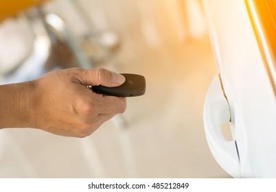 a hand holding a car's remote control pointing to the door,copy space.