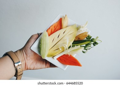 Hand holding carved Fruit Vegetables on dish, white background