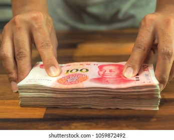 Hand holding cash yuan, Bundle of Chinese one hundred Yuan banknotes