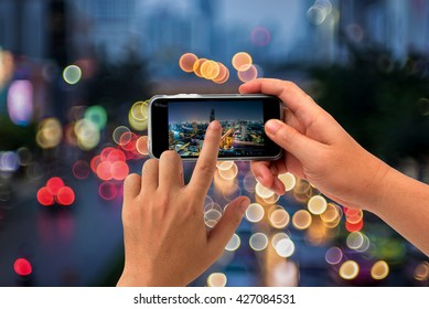 hand holding cell phone on city and bokeh  light  background