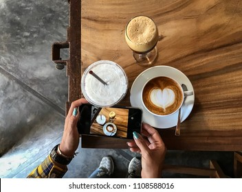 Hand holding cell phone to take photo coffee on the wooden table, top view and blurred background