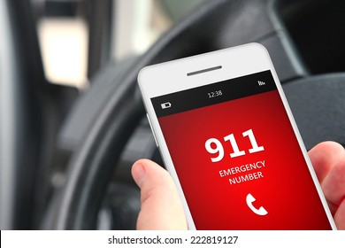hand holding cellphone with emergency number 911 in car