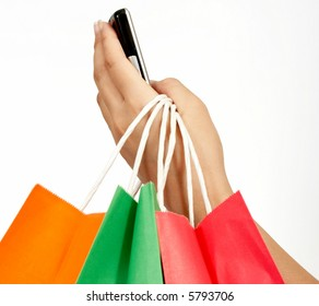a hand holding a cellphone and some shopping bags